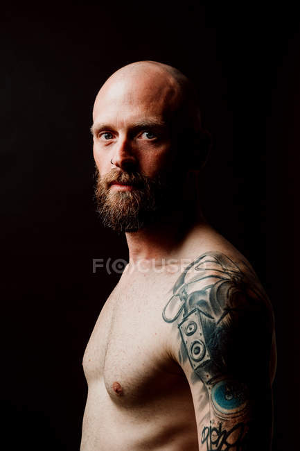 Side view of shirtless bald serious hipster with tattoos on hands looking at camera on black background — стокове фото