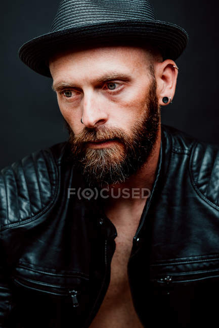 Cool hipster in hat and leather jacket looking away on black background — Stock Photo