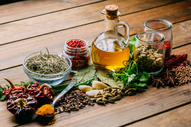 Assorted spices and herbs and bottle of oil placed on wooden tabletop — Stock Photo