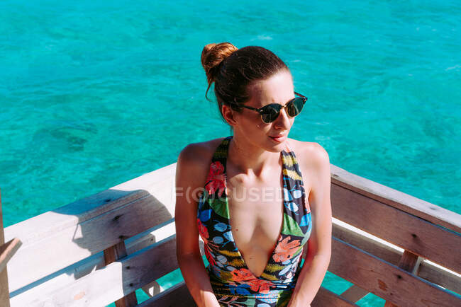 Lady in swimsuit and sunglasses sitting on seat near blue sea in Jamaica — Stock Photo