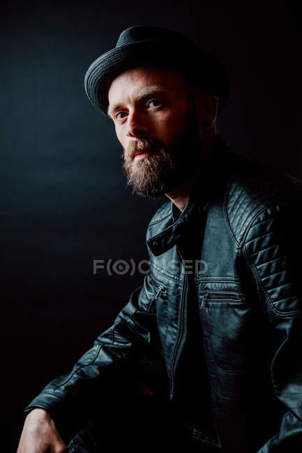 Hipster legal em chapéu e jaqueta de couro olhando para a câmera no fundo preto — Fotografia de Stock