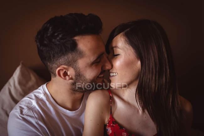 Couple heureux assis sur le lit — Photo de stock