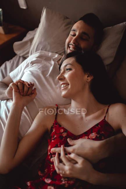 З вище красивий чоловік посміхається і обіймає красиву жінку, лежачи на зручному ліжку разом. — стокове фото