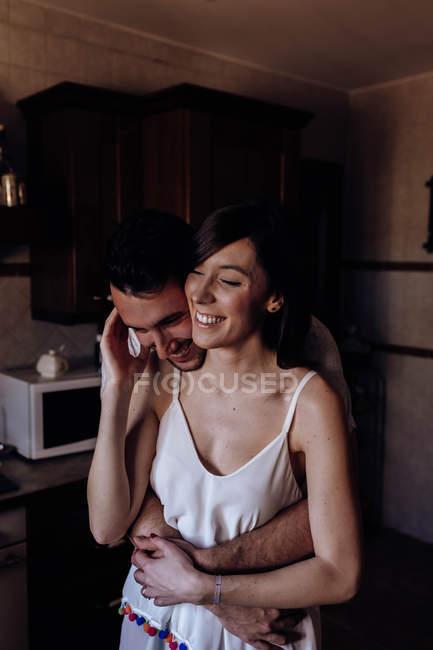 Feliz pareja abrazándose en la cocina - foto de stock