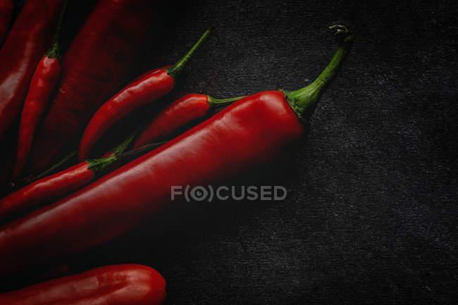 Frische rote würzige Chilischoten auf schwarzem Hintergrund — Stockfoto