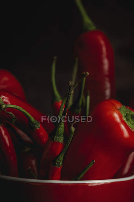 Nahaufnahme von frischen roten, würzigen Chilischoten in Tasse auf schwarzem Hintergrund — Stockfoto
