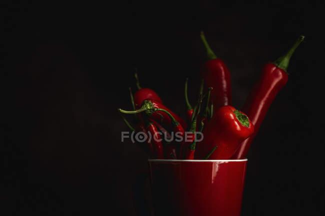 Frische rote würzige Chilischoten in Tasse auf schwarzem Hintergrund — Stockfoto