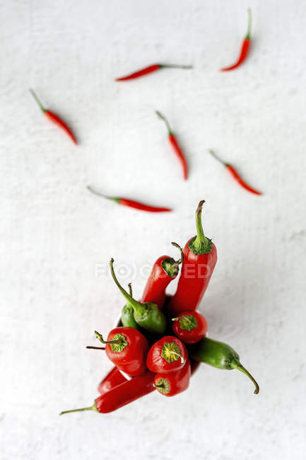 Fresh red and green spicy chilli peppers on white background — Stock Photo