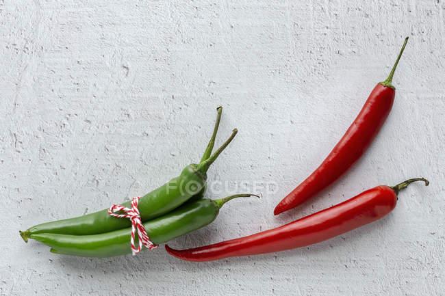 Frische rote und grüne würzige Chilischoten auf weißem Hintergrund — Stockfoto