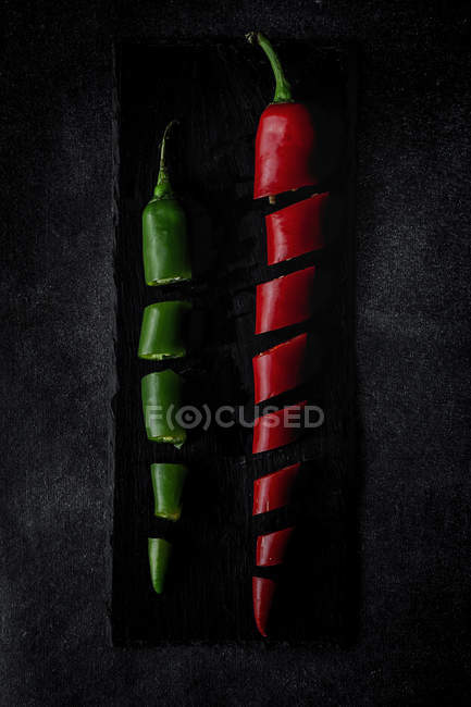 Fresh red and green sliced chilli peppers on slate on black background — Stock Photo