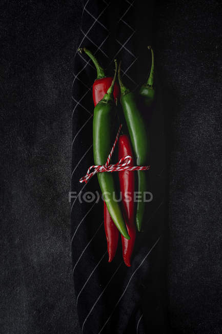 Fresh tied with twine red and green spicy chilli peppers on kitchen towel on black background — Stock Photo
