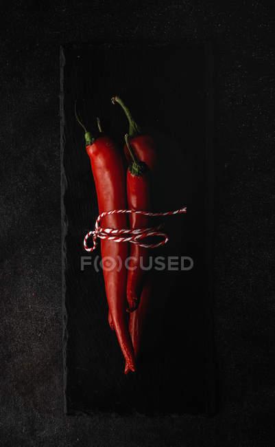 Pimientos picantes rojos frescos atados con torzal sobre pizarra sobre fondo negro - foto de stock