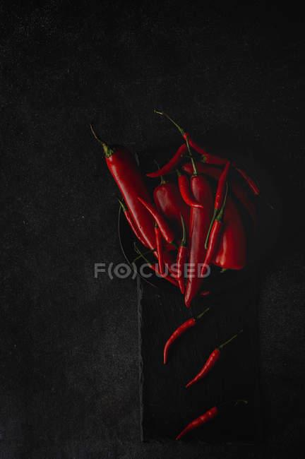 Frische rote würzige Chilischoten im Haufen auf Teller auf schwarzem Hintergrund — Stockfoto