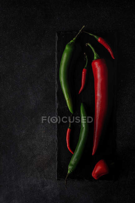 Fresh red and green spicy chilli peppers on slate on black background — Stock Photo