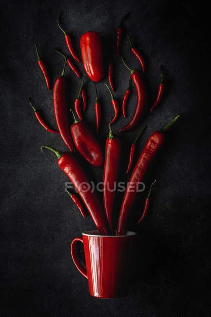 Свежий красный острый перец чили и кружка на черном фоне — стоковое фото