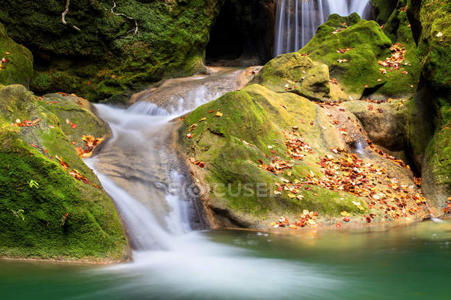 Turquoise water in reservoir with waterfall and green rocks, Navarra — Stock Photo