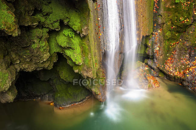 Agua turquesa en embalse con cascada y rocas verdes, Navarra - foto de stock