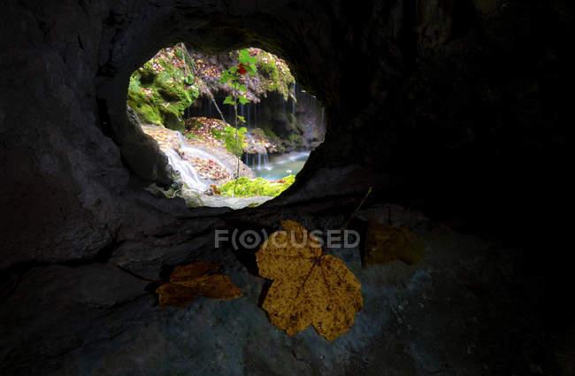 Перегляд через отвір у скелі невеликого водоспаду і скель — стокове фото