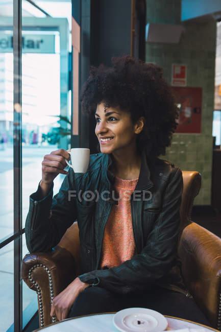Schwarze Frau mit Afro-Haaren trinkt einen Kaffee in einem Café — Stockfoto