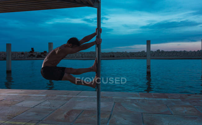 Young shirtless sportsman balancing on pole near water in evening — Stock Photo