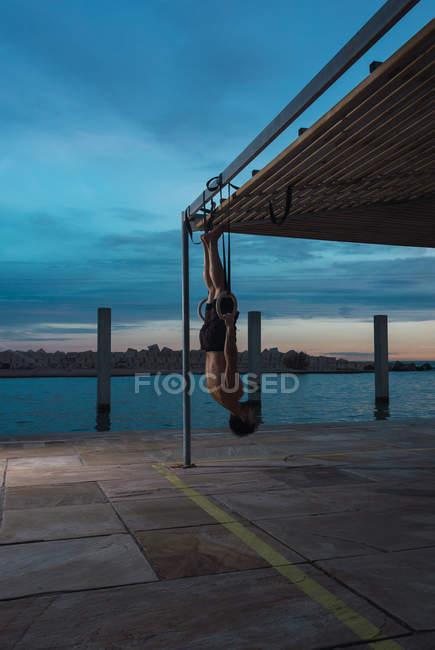 Uomo atletico in equilibrio su anelli ginnici su argine in città — Foto stock