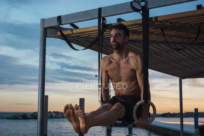 Hombre atlético balanceándose en anillos gimnásticos en terraplén en la ciudad nocturna - foto de stock