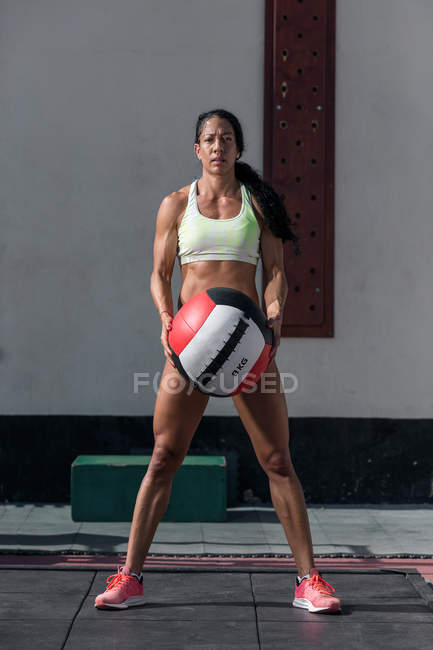 Confident muscular woman standing with training ball — Stock Photo