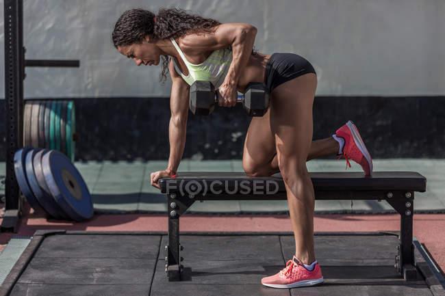 Концентрований м'язової жінка навчання з гантелями в тренажерний зал — Stock Photo