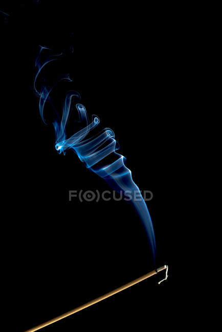 Remolinos de humo azul brillante sobre fondo negro - foto de stock