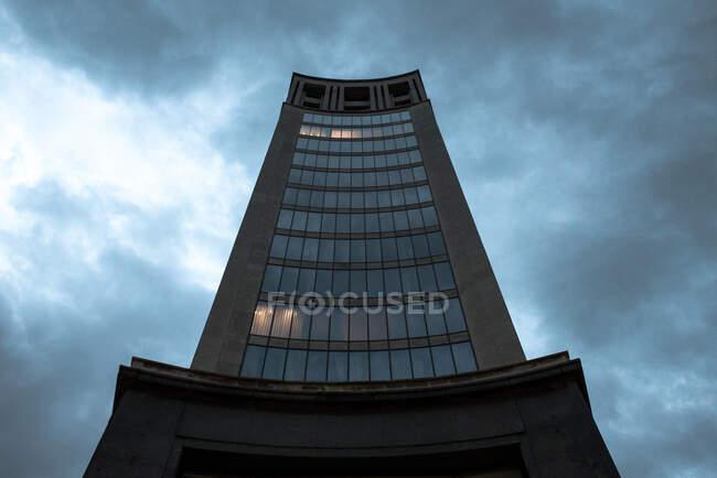Vista prospectiva de baixo do edifício alto da torre com fachada de pedra e janelas sob céu nublado, Astúrias — Fotografia de Stock