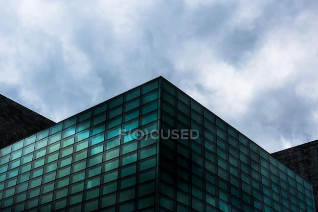 Dal basso di vetro esterno edificio con design futuristico vetro sotto cielo nuvoloso — Foto stock