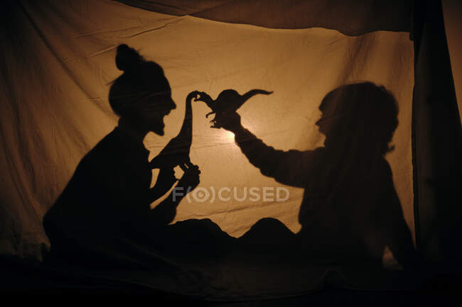 Silhouette of woman with kid playing behind sheet — Stock Photo
