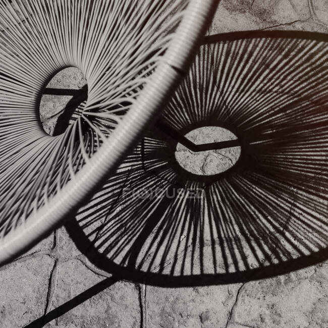 Black and white of contemporary circular wicker chair and its shadow on stone pavement in sunlight — Stock Photo