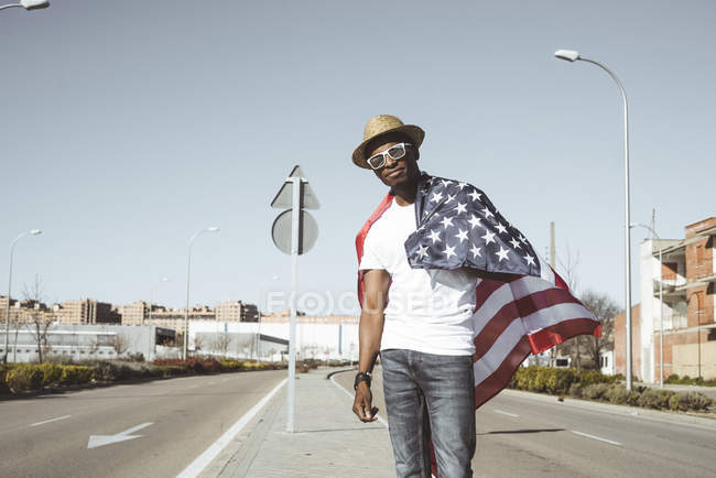 Happy black man with flying American flag — Stock Photo