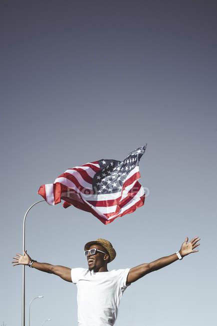 Homem preto exaltado em óculos de sol e chapéu segurando as mãos com bandeira americana voando acima da cabeça no céu azul — Fotografia de Stock