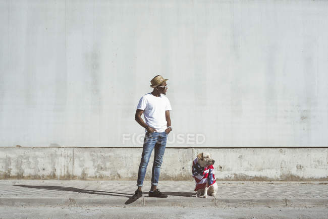 Stylish black man with Labrador wrapped in colorful American flag on concrete street in sunlight — Stock Photo