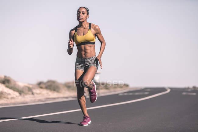 Ethnic sportswoman running on desert road — Stock Photo