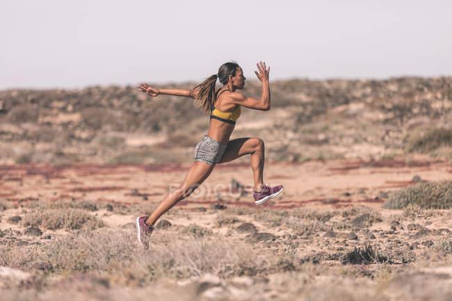 Ethnic sportswoman running in sunny desert — Stock Photo