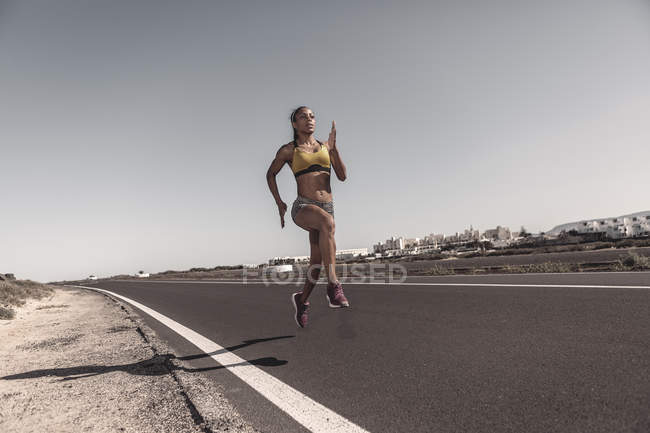 Ethnic sportswoman running on road in countryside — Stock Photo