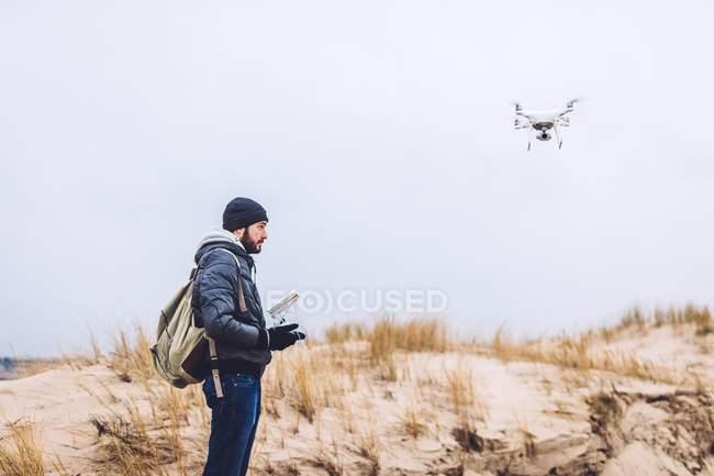 Jeune garçon avec télécommande fonctionnement drone volant sur la côte — Photo de stock