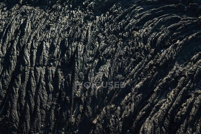 Textura de close-up de rocha escura áspera na luz solar — Fotografia de Stock