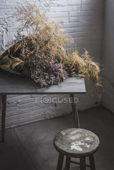 Bouquet of dry coniferous twigs in craft paper on table in grey murk room with brick walls — Stock Photo