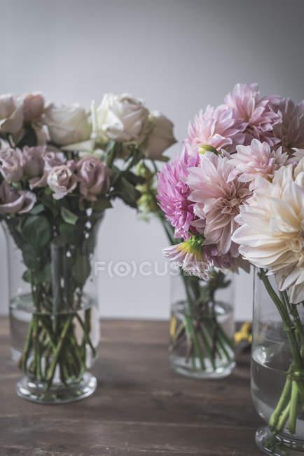 Holztisch mit Geschirr und Sträußen frischer Blüten in Vasen mit Wasser in der Nähe der weißen Wand — Stockfoto