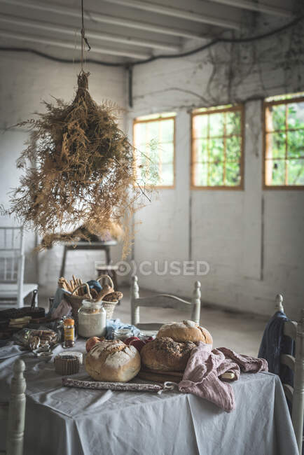 Bunch of dry coniferous twigs hanging on twist above table with bakery near chairs in room — Stock Photo