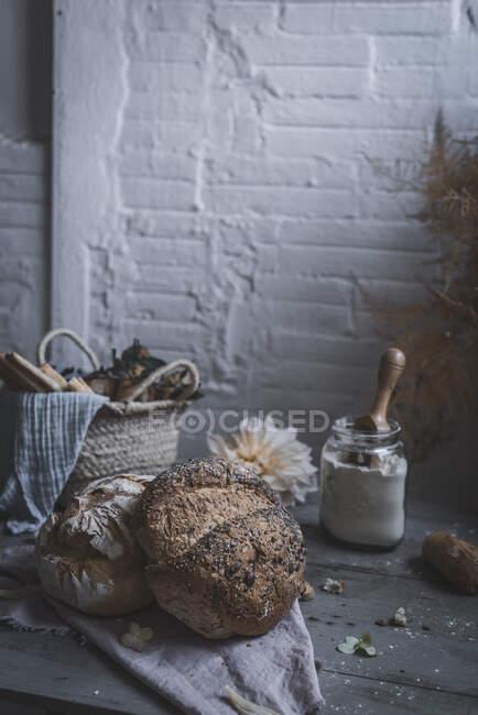 Bouquet de brindilles de conifères sèches suspendues sur la torsion au-dessus de la table avec boulangerie près des chaises dans la chambre — Photo de stock