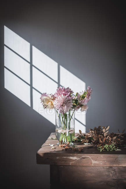 Wooden table with bouquet of pink chrysanthemums in vase between fallen petals and white wall with sunshine — Stock Photo