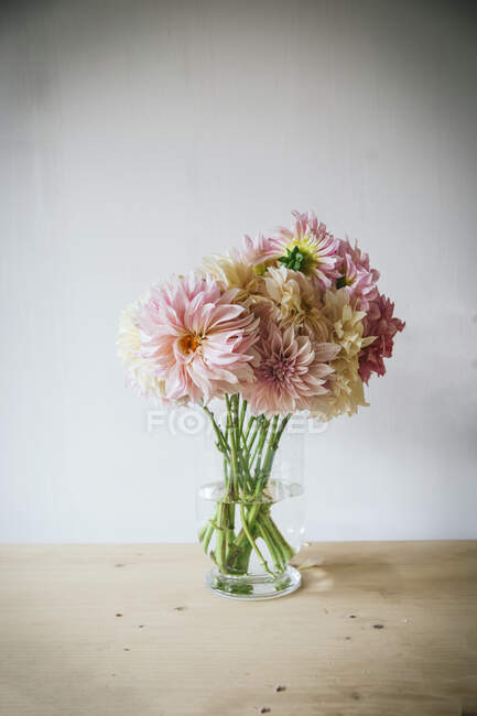 Wooden table with kitchenware and bouquet of fresh blooms in vase with water near white wall — Stock Photo