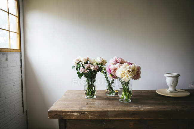 Wooden table with kitchenware and bouquets of fresh blooms in vases with water near white wall — Stock Photo