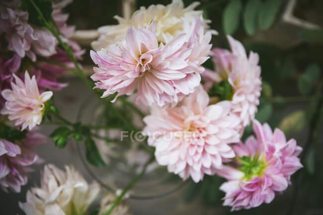 Деревянный стол с кухонной утварью и букет свежих цветов в вазе с водой возле белой стены — стоковое фото