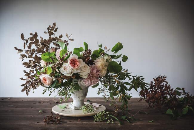 Concept de bouquet de roses sèches et fraîches, de chrysanthèmes et de brindilles de plantes en vase rétro sur planche de bois sur fond gris — Photo de stock